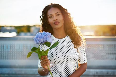 Pretty afro americanlady presenting a flower