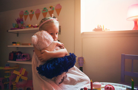 Cute little girl hugging her toy bear