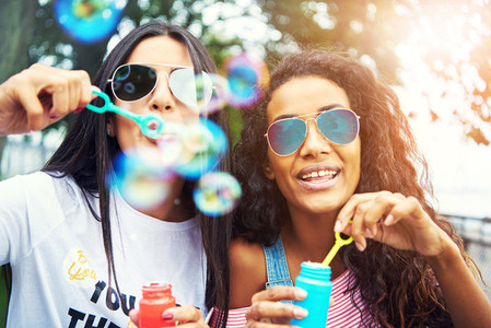 Diverse friends blow bubbles at the camera