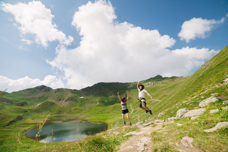 Young couple jumping in a big valley with a lake