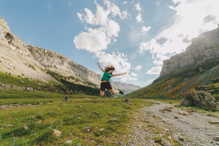 Young redhead woman jumping in a big valley