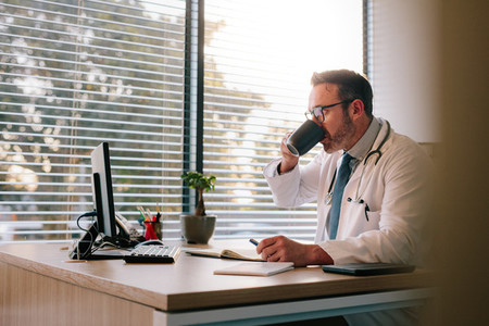 Doctor working at his office desk and drinking coffee