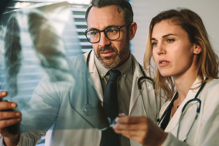 Doctor and surgeon closely studying x ray of patient