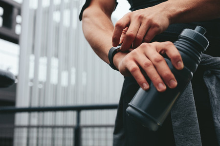 Man with water bottle using a smartwatch to monitor his progress
