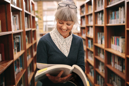Smiling senior woman looking at a book standing in a library
