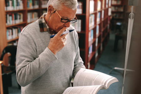 Portrait of a senior man standing in class holding a text book