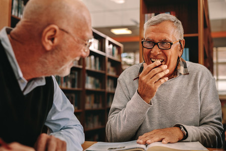 Senior men sitting in a library and studying