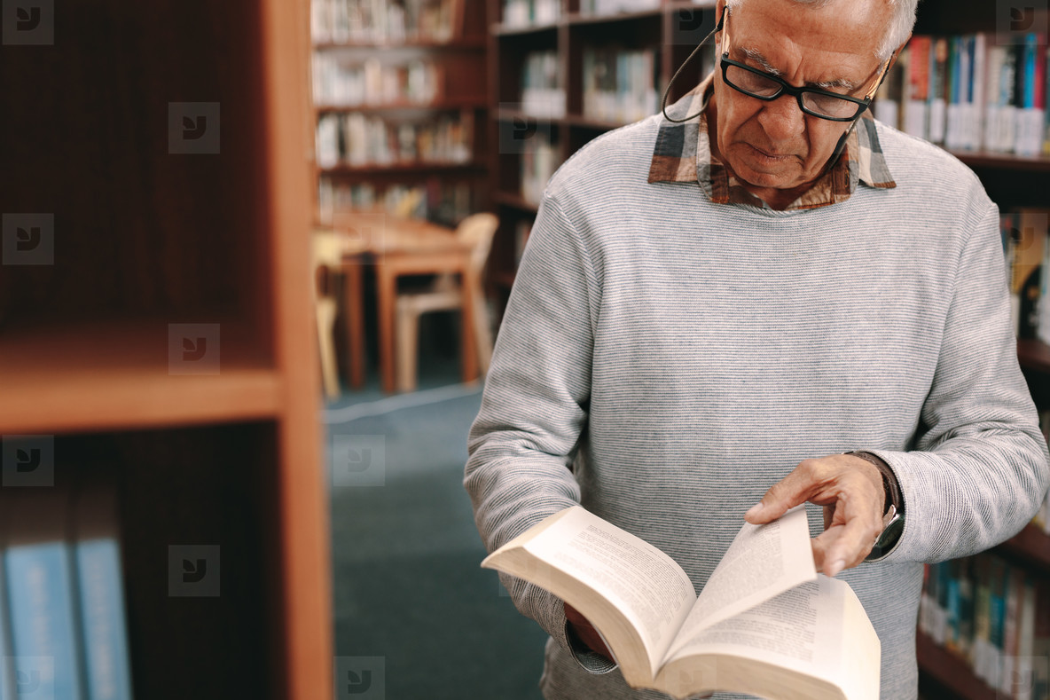Portrait of a senior man looking at a book in library