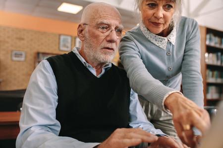 Senior man and woman looking at a computer screen
