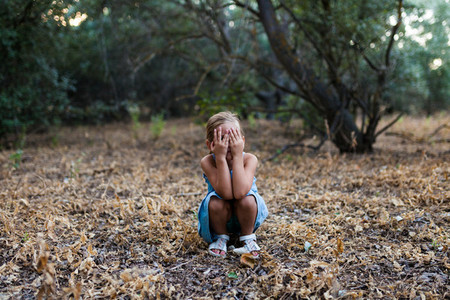 Lonely sad little girl squatting in the forest