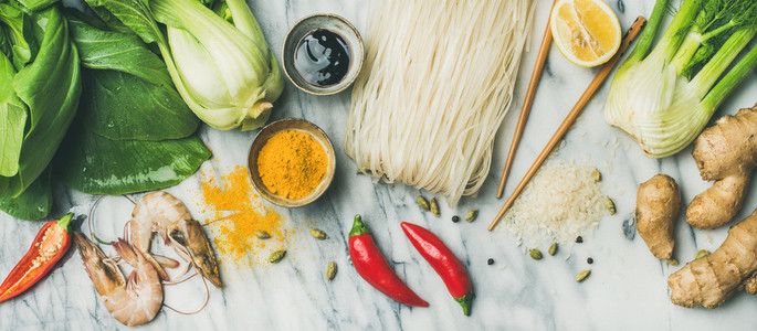 Flat lay of Asian cuisine ingredients over grey marble background