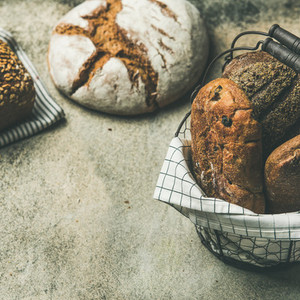 Various bread loaves on grey concrete background square crop