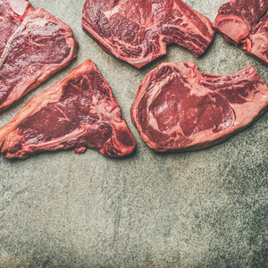Porterhouse t bone and rib eye steaks over grey background square crop