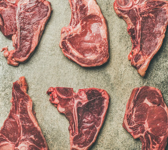 Flat lay of fresh raw beef meat steaks grey background