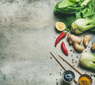 Flat lay of Asian cuisine ingredients over grey concrete background