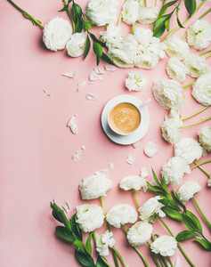 Flat lay of cup of coffee and ranunculus flowers copy space