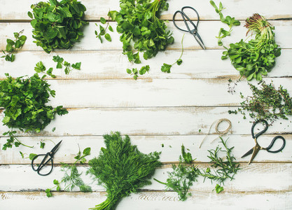 Various fresh green kitchen herbs over wooden background  copy space
