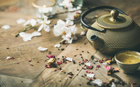 Iron teapot cups dried rose buds blooming almond flowers candles