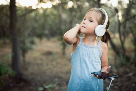 Little girl listening music with her headphones in the forest