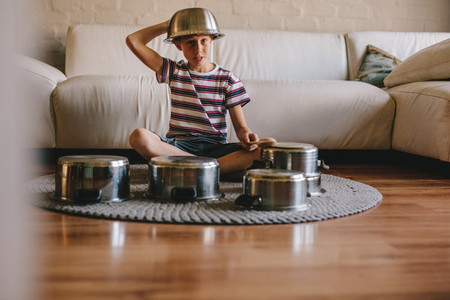 Future drummer boy with cooking pots at home