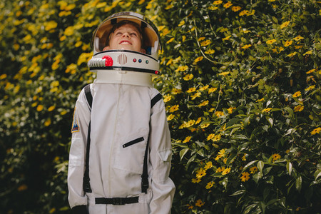 Cute boy in astronaut dress playing outdoors