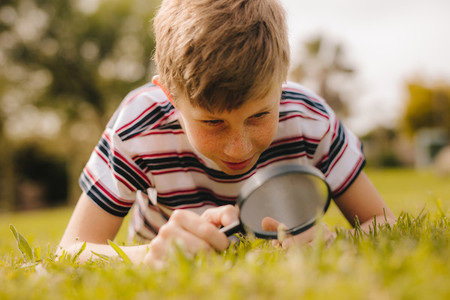 Boy exploring garden with his magnifier