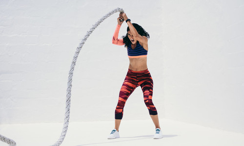 Fitness woman working hard on a battle rope