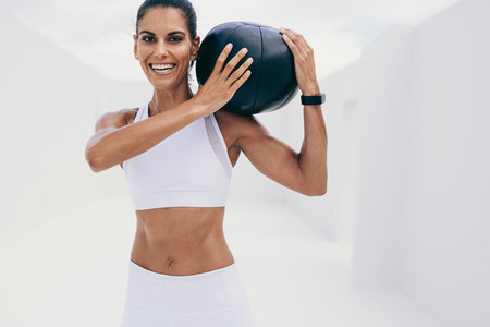 Smiling fitness woman doing workout using a medicine ball