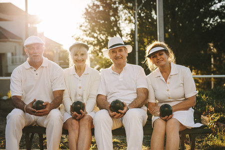 Senior friends sitting outdoors with boules in hand