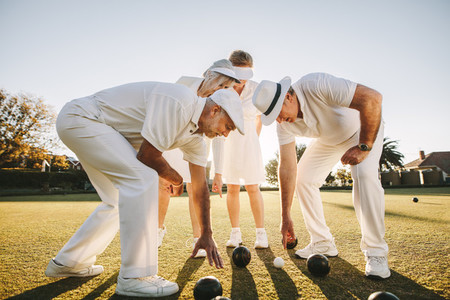 Group of senior men and women playing boules in a lawn