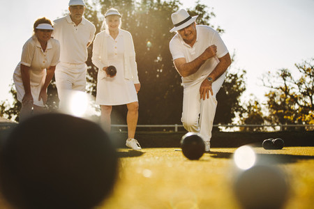 Senior people playing boules in a park