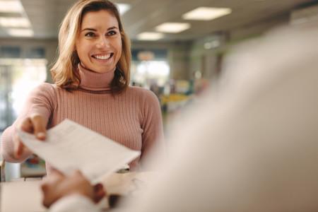 Female customer giving prescription to pharmacist