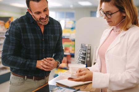 Pharmacist giving advice over a medicine to customer