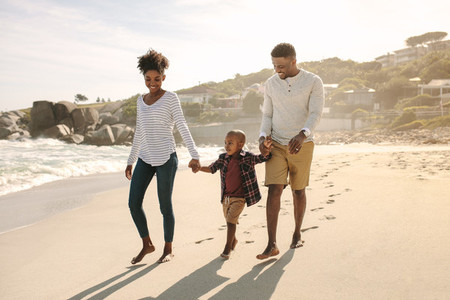 Family with son walking along the beach