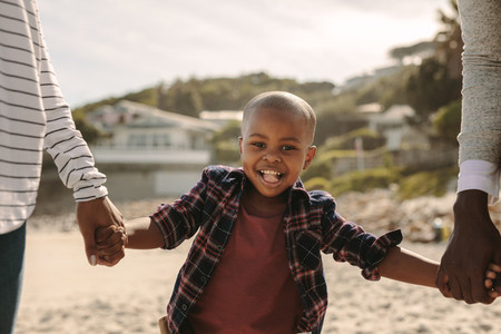 Smiling boy walking with parents on the beach