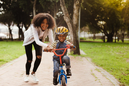 Mother teaching son to ride bicycle