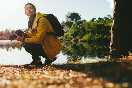 Tourist sitting near a lake with a dslr camera