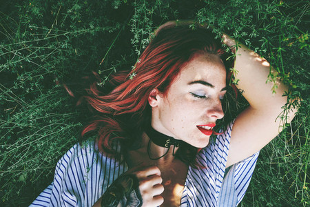 Young and beautiful redhead woman posing surrounded by nature