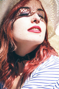 Redhead model protecting herself from sun with a hat in summer