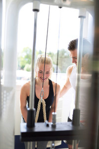 Male Trainer Assisting a Woman Pulling Pulley Down