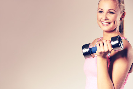 Young woman holding dumbbell