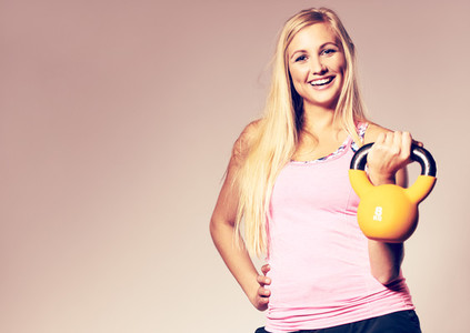 Woman wearing workout clothes holding a kettlebell