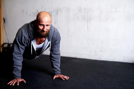 Muscular man smiling at camera while doing pushup