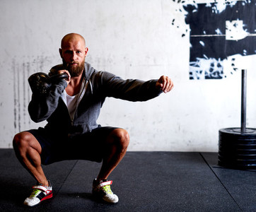 Athletic white man squatting with kettlebells
