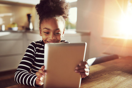 Happy little ethnic black girl reading on a tablet