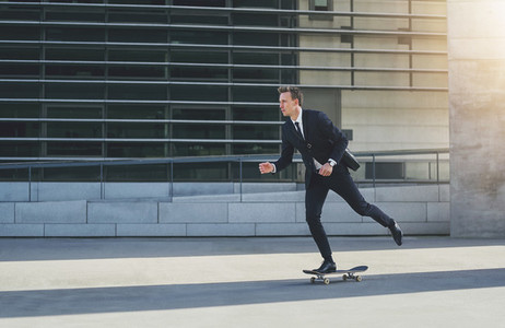 Businessman on a skateboard in urban area