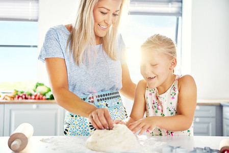 Excited little girl helping her mother make pastry
