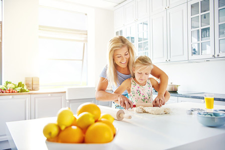 Mother teaching her little daughter to bake