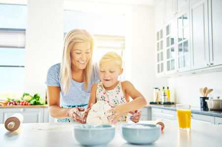Happy child learning to bake with her mother