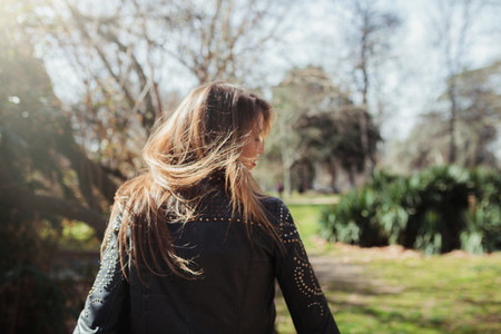 Young blonde woman from behind moving her hair in the park